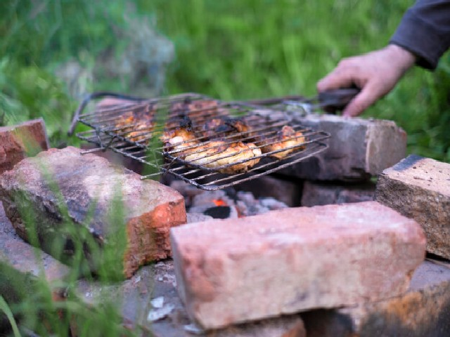 Man Cooking Meat Barbecue On The Chicken Grill In His Garden On Simple Bricks