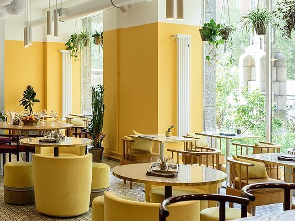 o amarelo das paredes alguns bancos junto ao verde das plantas e o laranja da mesa deixam o ambiente mais suave