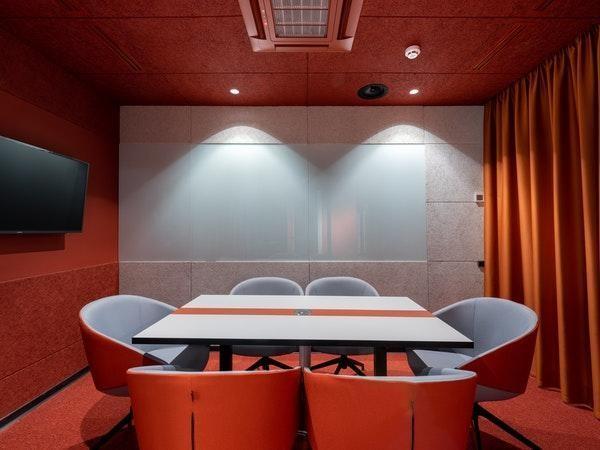 tinta vermelha da parede junto ao laranja da cortina e cadeiras fazem o ambiente mais quente